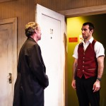 Carmichael (Rod Gnapp*) questioned by curious hotel receptionist, Mervyn (Alex Hurt)