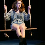 Nina (Martha Brigham*) sits alone on the swing.