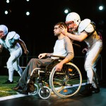 Mike, in a wheelchair, (Jason Stojanovski) and his younger self (Thomas Gorrebeeck*) view playbacks of the defining play that changed his life.