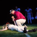 Coach (Dave Maier*) examines young Mike (Thomas Gorrebeeck*) after a devastating hit.