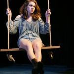 Nina (Martha Brigham*) sits alone on the swing.