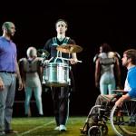 Jerry (Wiley Naman Strasser) attempts to rehabilitate Mike (Jason Stojanovski), as the halftime show begins (Drummer: Alex Hersler).